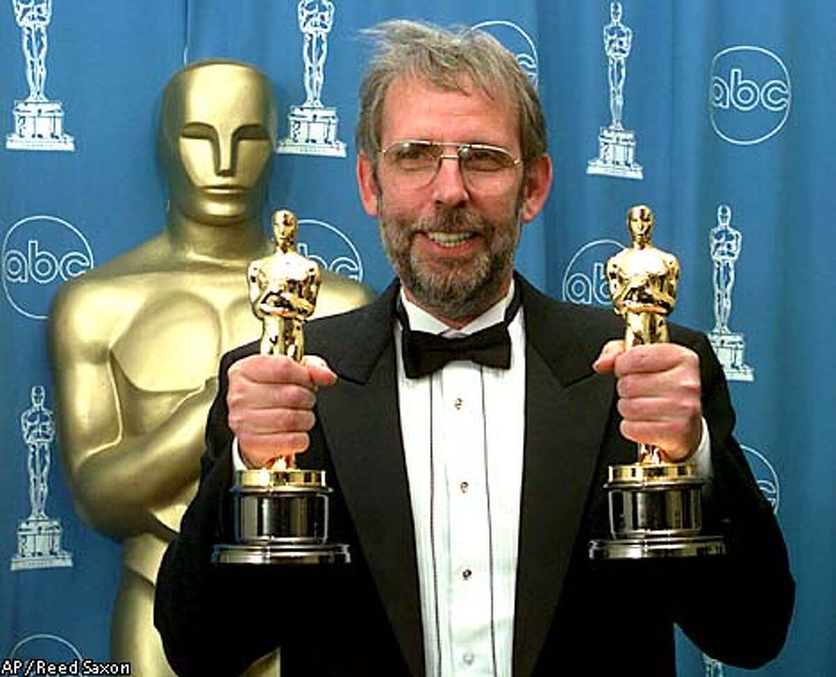 holds his two Oscars while posing for photographers at the 69th Annual Academy Awards in Los Angeles Monday, March 24, 1997. Murch won an Oscar for Achievement in Sound and Achievement in Film Editing for