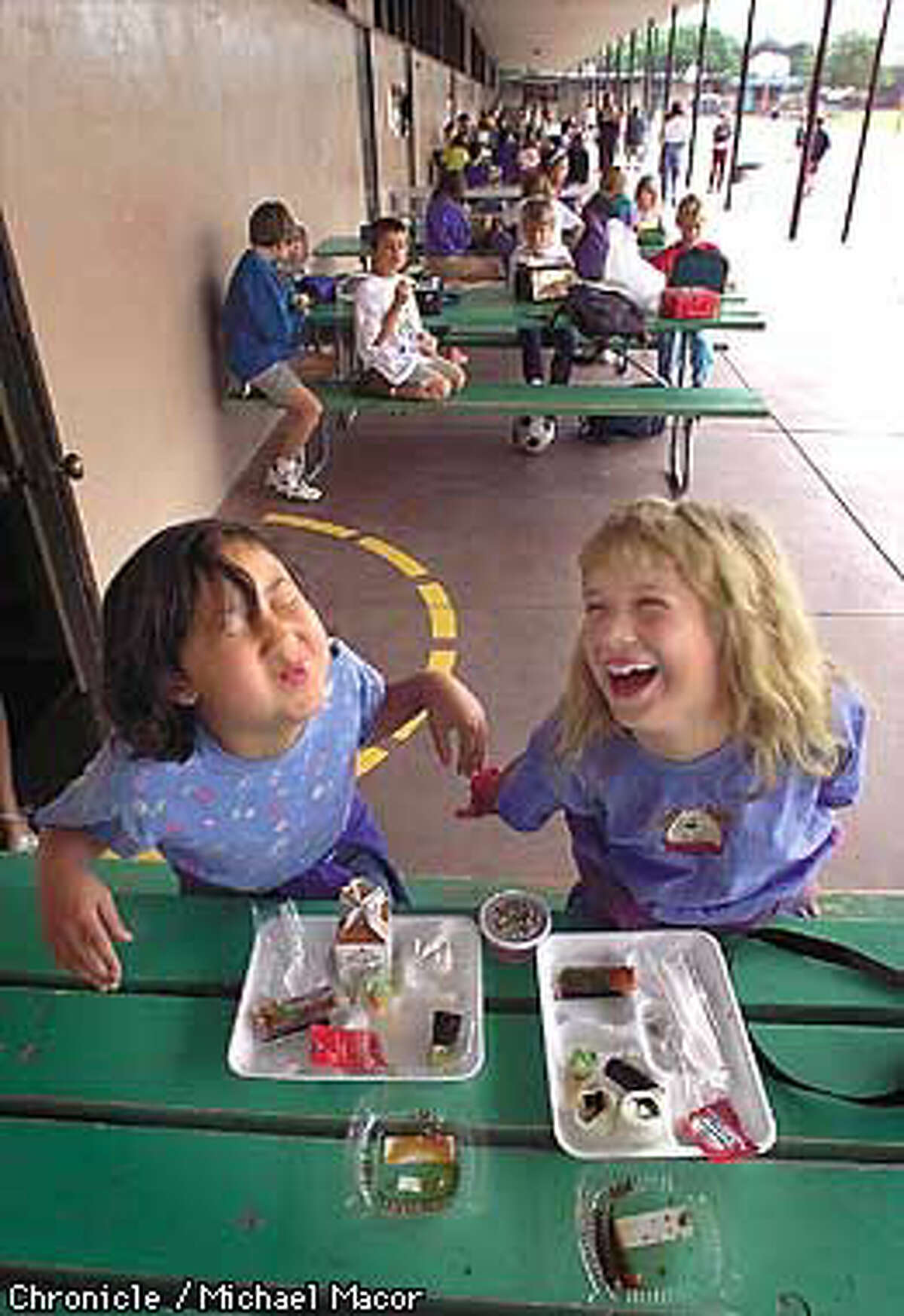 Alicia Michelson (left) and Cally Berg, third-graders at Ohlone Elementary School in Palo Alto, enjoyed their California rolls at lunch. Chronicle Photo by Michael Macor