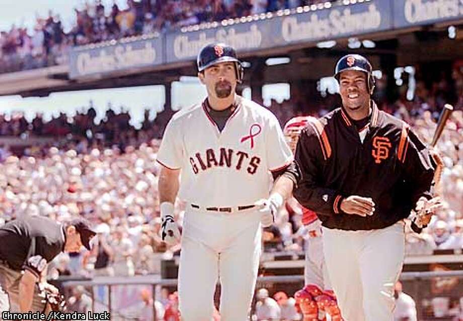 After the Giants' Rich Aurilia hits a homer in the 3rd he and Livan Hernandez come off the field after both scoring during their game against the Philadelphia Phillies, the Giants won 8-5. (KENDRA LUCK/SAN FRANCISCO CHRONICLE) Photo: KENDRA LUCK