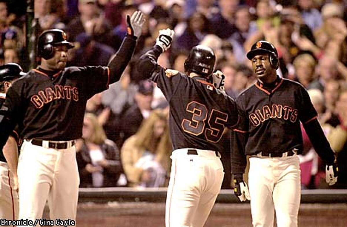 Rich Aurelia is congratulated by Barry Binds and Shawon Dunston after hitting two run home run in the bottom of the sixth to put the Giants ahead by two. Photo by Gina Gayle/The SF Chronicle.
