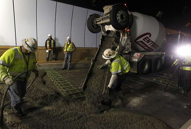 Construction workers pour concrete for the northbound lane of the Devil's Slide tunnel. Caltrans expects to open the two bores to Highway 1 traffic by the end of the year. Photo: Paul Chinn, The Chronicle