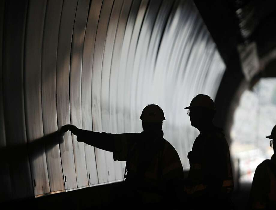 Construction workers inspect the coated steel plates lining the southbound bore of the Devil's Slide tunnel project in Pacifica, Calif. on Tuesday, Jan. 31, 2012. Caltrans is hoping to open the two bores to traffic by the end of the year. Photo: Paul Chinn, The Chronicle