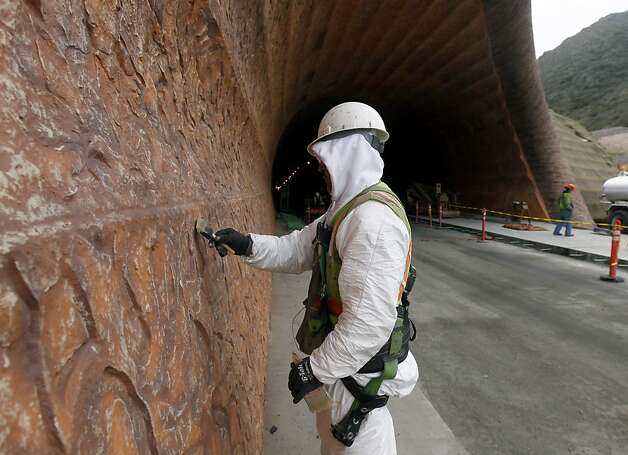 A painter touches up the decorative retaining wall at the north portal of the Devil's Slide tunnel project in Pacifica, Calif. on Tuesday, Jan. 31, 2012. Caltrans is hoping to open the two bores to traffic by the end of the year. Photo: Paul Chinn, The Chronicle