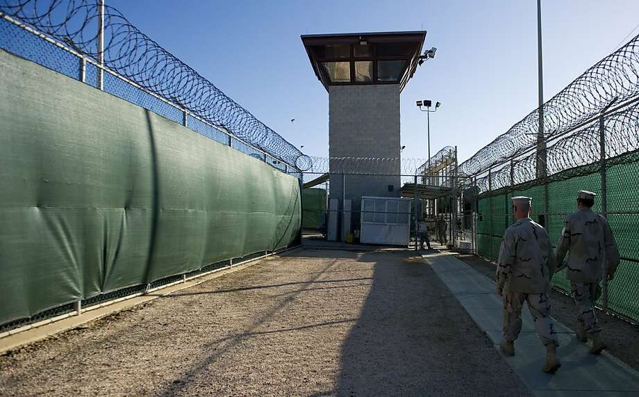 "This image reviewed by the US military, show two members of the military walking out of the ""Camp Six"" detention facility of the Joint Detention Group at the US Naval Station in Guantanamo Bay, Cuba, January 19, 2012. Photo: Jim Watson, AFP/Getty Images"