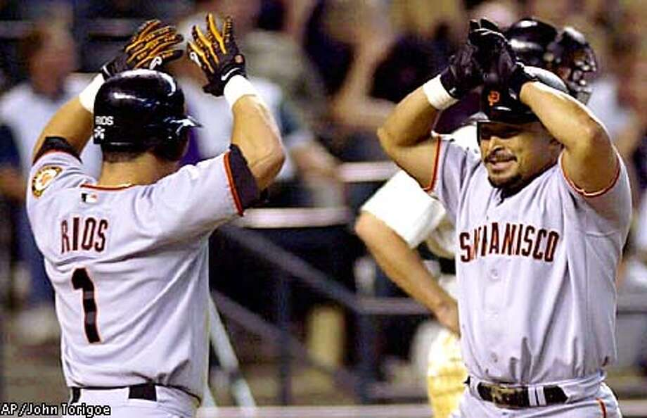 San Francisco Giants' Armando Rios high fives Marvin Benard on his two run homer off of Arizona Diamondbacks pitcher, Byung-Hyun Kim in the top of the ninth inning Sunday, July 29, 2001, at Bank One Ballpark in Phoenix. The Giants defeated the Diamondbacks 4-3 to complete the four game sweep. (AP Photo/John Torigoe)) Photo: JASON WISE