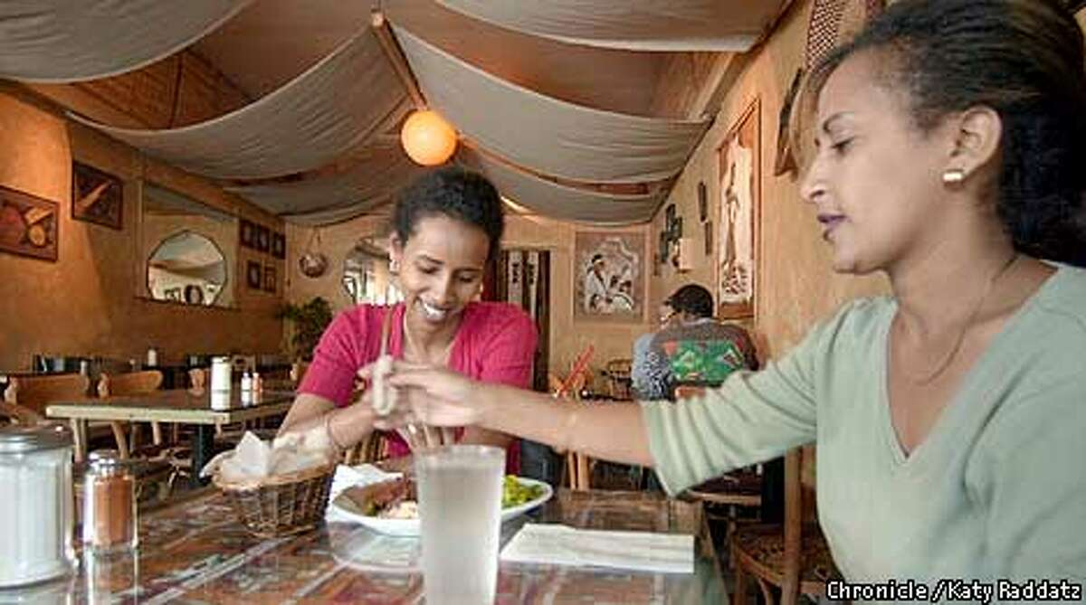 EBCOLUCCI27a-C-18JUL01-EF-RAD Photo by Katy Raddatz--The Chronicle Cafe Colucci at 6427 Telegraph Ave. in Oakland serves wonderful Ethiopian food. Shown: dining room, with Lily Aelise (L) and Tsige Girma (R) enjoying their lunch of kitfe.