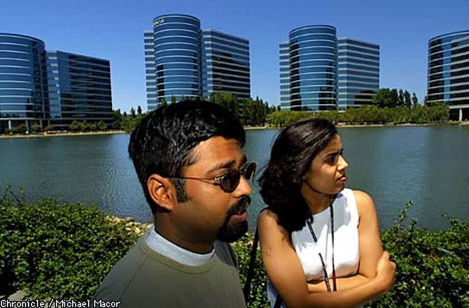 "Jeydev Rajamini, left, Software Developement Manager and Pramodini Gattu, Software Developer, both work for ORACLE in Redwood Shores. Mood of workers in the Silicon Valley the day after major players like ""Hewlett-Packard"" and ""JDS Uniphase"" announced layoffs after hugh losses. by Michael Macor/The Chronicle Photo: MICHAEL MACOR"