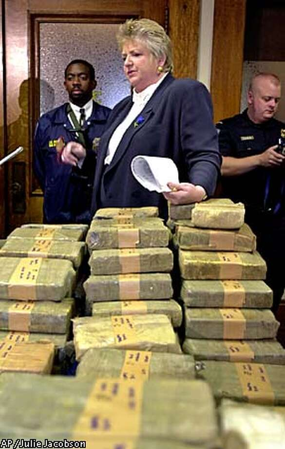 During a news conference in San Francisco, Tuesday, July 24, 2001, San Francisco customs port director Alice M. Rigdon stands behind 199 bricks of cocaine while answering questions about the 515 pounds of the drug that were seized Saturday morning, July 21, 2001, from an oil tanker docked in San Francisco Bay. According to the Port of San Francisco, the seized cocaine has an estimated street value of about $4.5 million. (AP Photo/Julie Jacobson) Photo: JULIE JACOBSON