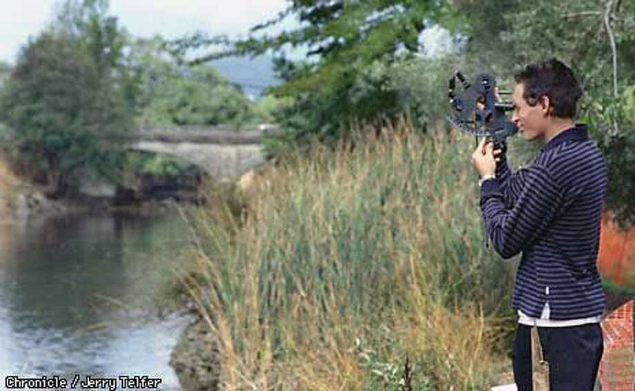 On the banks of the Napa River, Nick Ray takes measurements for a mapmaking project at the Oxbow School, a semester-long art-intensive program for high school students. Chronicle Photo by Jerry Telfer