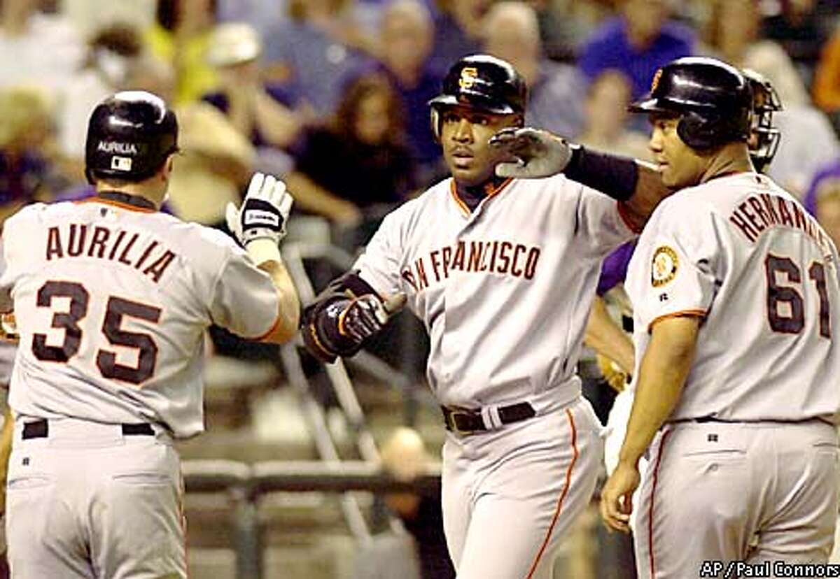 San Francisco Giants slugger Barry Bonds, center, is congratulated by teammates Rich Aurilia, left, and Livan Hernandez, right, after hitting a grand slam off Arizona Diamondbacks pitcher Curt Schilling in the fifth inning Thursday, July 26, 2001, at Bank One Ballpark in Phoenix. The home run was Bonds' 44th of the season and second of the game.(AP Photo/Paul Connors)