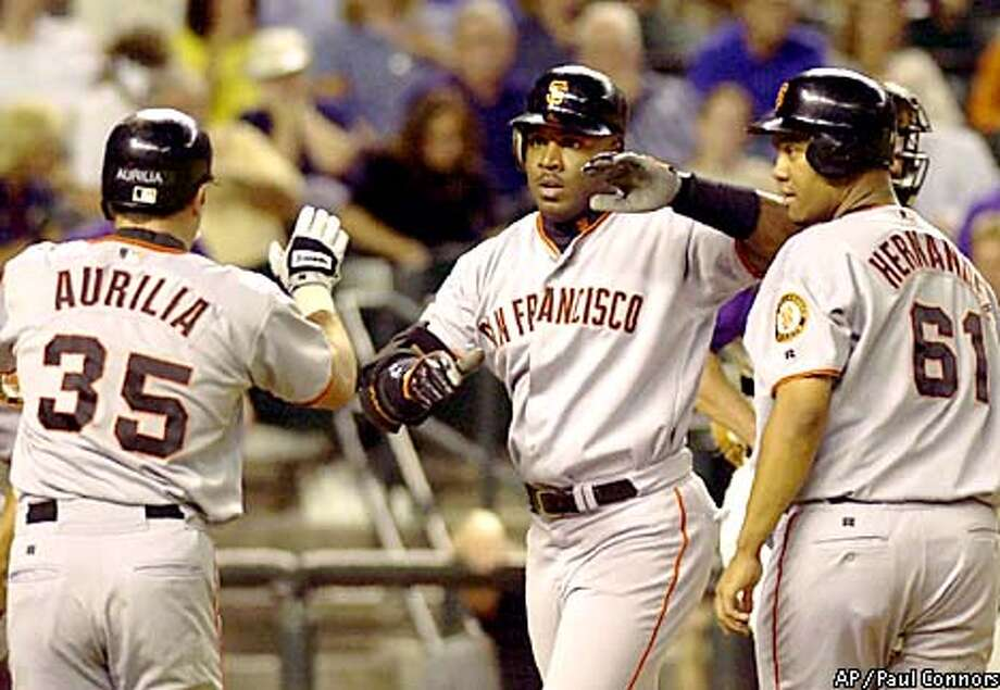 San Francisco Giants slugger Barry Bonds, center, is congratulated by teammates Rich Aurilia, left, and Livan Hernandez, right, after hitting a grand slam off Arizona Diamondbacks pitcher Curt Schilling in the fifth inning Thursday, July 26, 2001, at Bank One Ballpark in Phoenix. The home run was Bonds' 44th of the season and second of the game.(AP Photo/Paul Connors) Photo: PAUL CONNORS