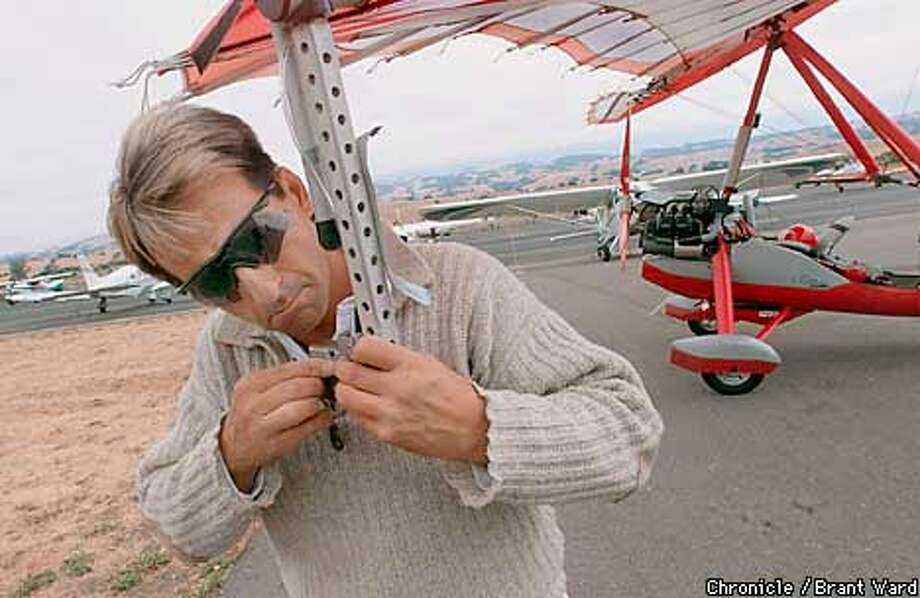"Adventurer Michael Globensky readies his ""trike"" at the Petaluma Airport recently. As a souvenir for those who want to fly in his two-seat ultralight, Glovensky attaches a small camera to the wing, but today the camera didn't work. By Brant Ward/Chronicle Photo: BRANT WARD"