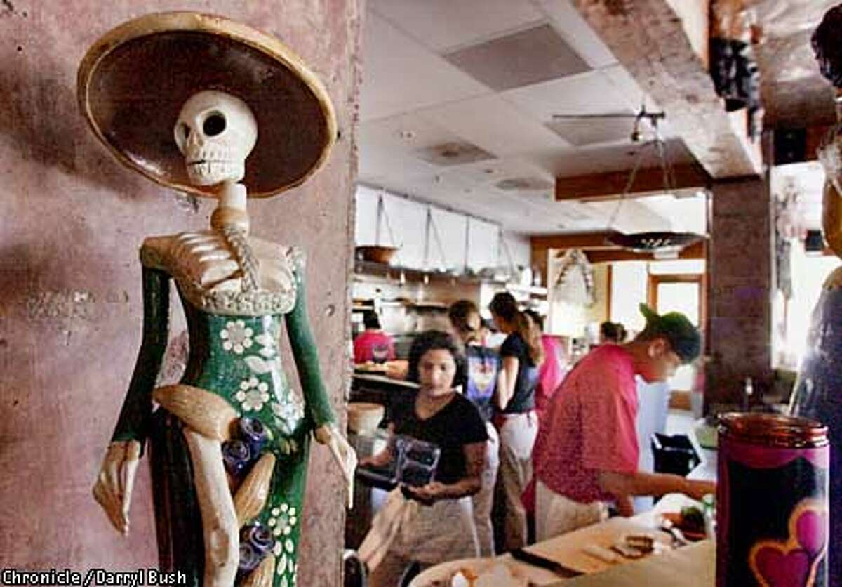 PNMILAGROS20A-C-11JUL01-PF-DB A figurine decorates the restaurant Milagros in Redwood City, as waiters and cooks work in the background. Chronicle Photo by Darryl Bush
