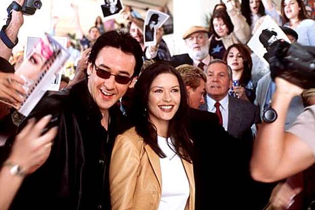 "John Cusack and Catherine Zeta-Jones play an unhappily married couple who reunite to promote a movie in ""America's Sweethearts."""