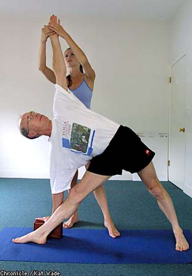 John Abbott, who bought Yoga Journal in 1997, assumed an asana (pose) under the guidance of yoga instructor Amy Stone. Chronicle photo by Kat Wade