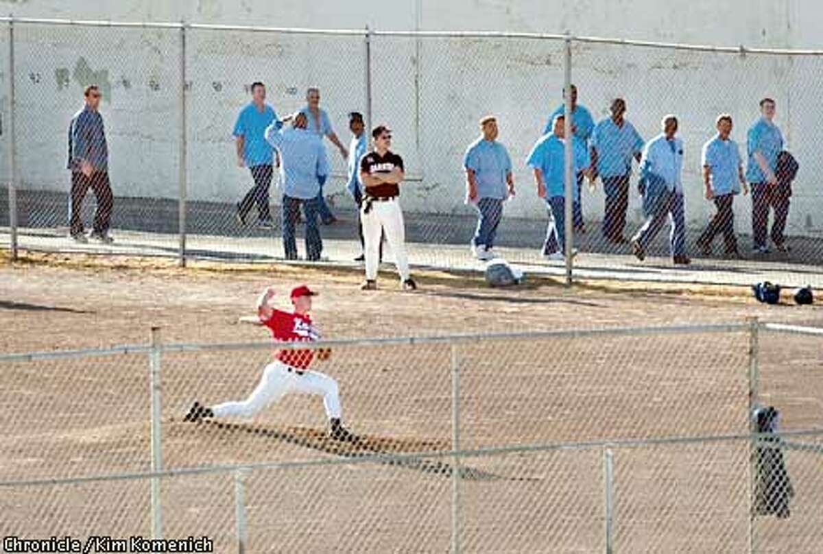QUENTINXXd-C-12JUL01-MN-KK The San Quentin Giants baseball team hosts the Novato Knicks. Knicks pitcher Rick Firebaugh pitches while inmates pass by on their way to church services. CHRONICLE PHOTO BY KIM KOMENICH