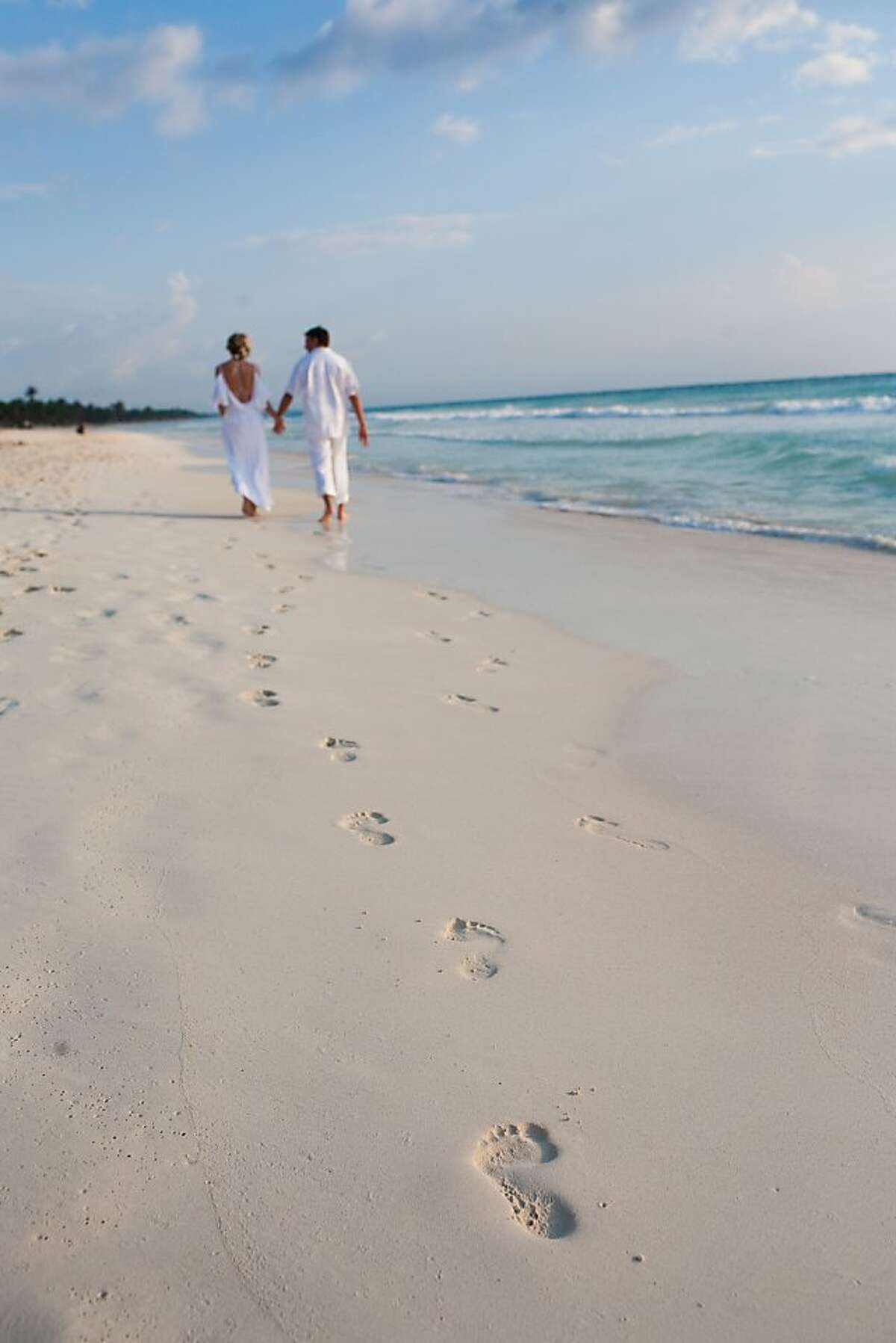 A bride and groom walk along the beach in Tulum.