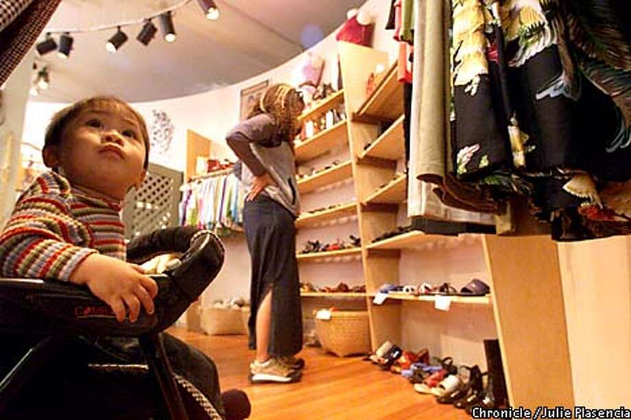 Rhea Fontaine checked out the wall of shoes with her nephew Juliao Ocampo at child-friendly Elements on College Avenue. Chronicle photo by Julie Plascencia