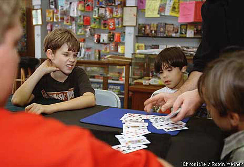 SLEIGHT OF HAND: Jason Robertson (left) and Tony Campbell keep their eyes on the cards as Ken Garr performs a trick during a free class at the Mostly Magic Shop in Santa Rosa Chronicle Photo by Robin Weiner
