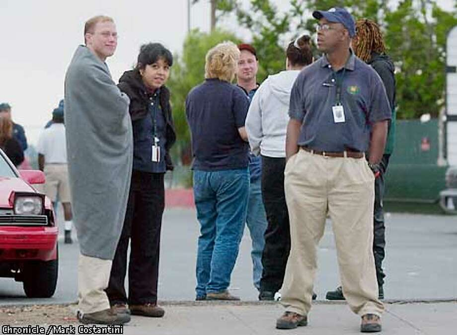 Employees wait across the street from the warre house for thier exit meeting. Webvan goes out of business. Photos taken at the company's Oakland warehouse facility on Coliseum Way. Photo: Mark Costantini/S.F. Chronicle Photo: Mark Costantini