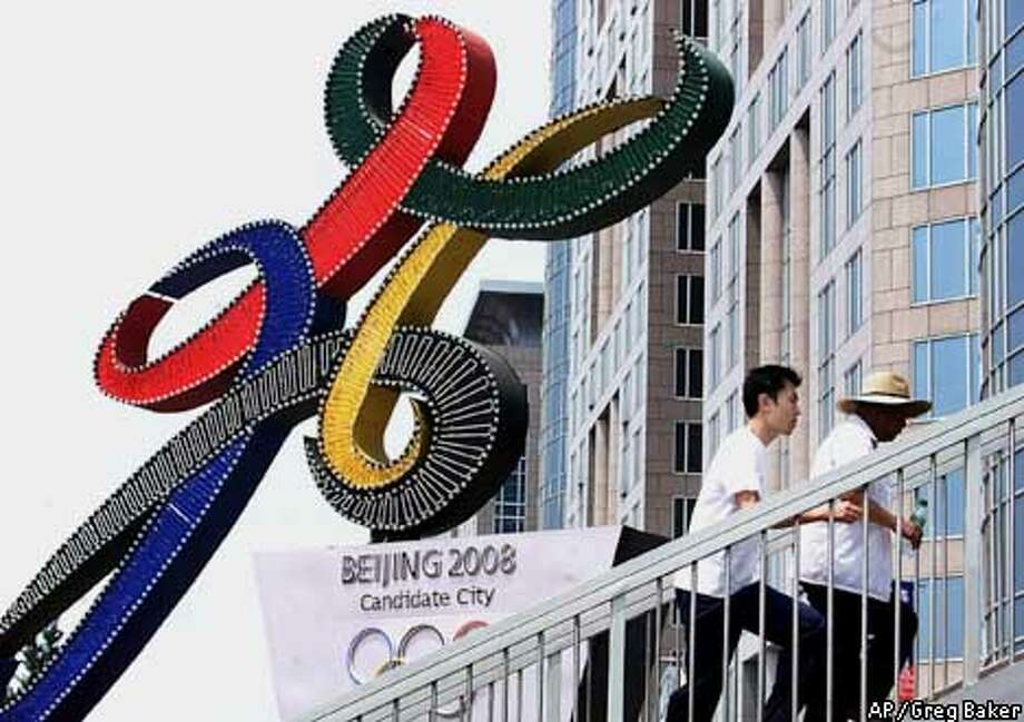 Chinese men walk past the logo for Beijing's bid for the 2008 Olympic Games, in Beijing, China, Saturday July 7, 2001. Beijing, the front-runner in a competition with Toronto, Paris, Osaka and Istanbul to host the 2008 games, will find out Friday whether its bid is successful. (AP Photo/Greg Baker) Photo: GREG BAKER