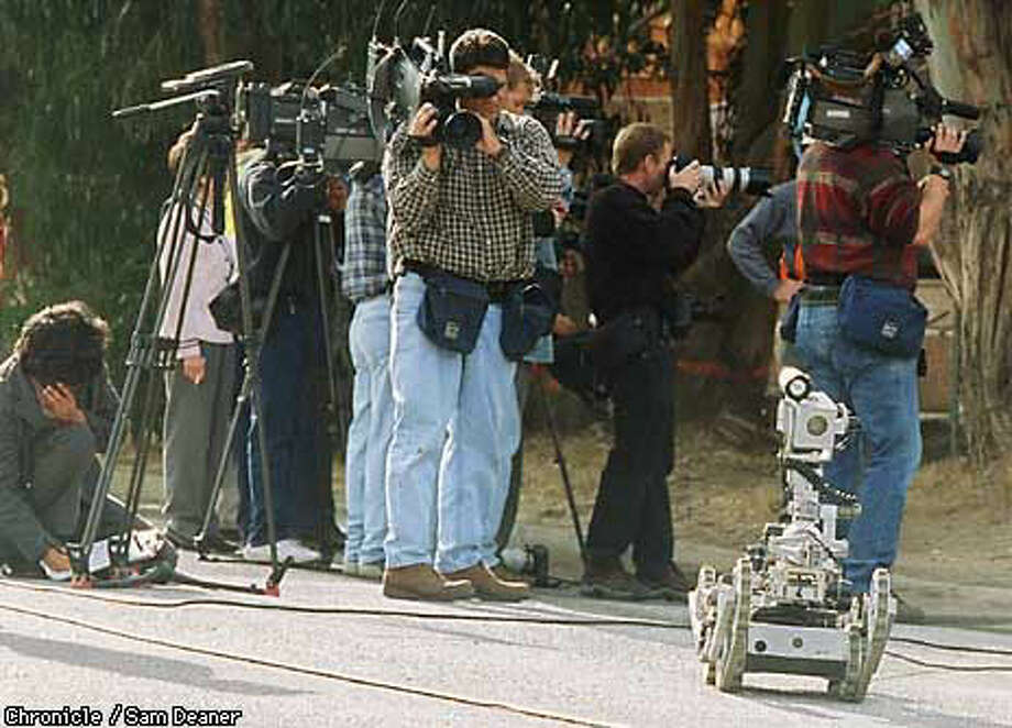 Photographers began to turn their attention elsewhere as a robot named Three Yellow Three, which had been used to examine an object that was suspected of being a pipe bomb in Millbrae. Chronicle Photo by Sam Deaner
