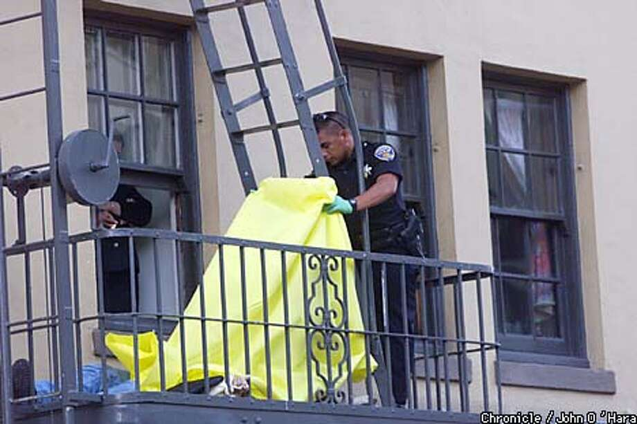 A San Francisco police officer looked at the body of the robbery suspect shot on a Tenderloin fire escape. Chronicle photo by John OL'Hara