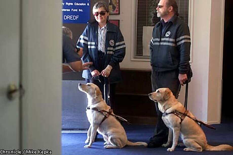 Constance Kelley and Claude Everett stood with their guide dogs Makasa, left, and Deb after a news conference in Berkeley. Kelley and Everett are suing Friendly Cab Co. Chronicle photo by Mike Kepka