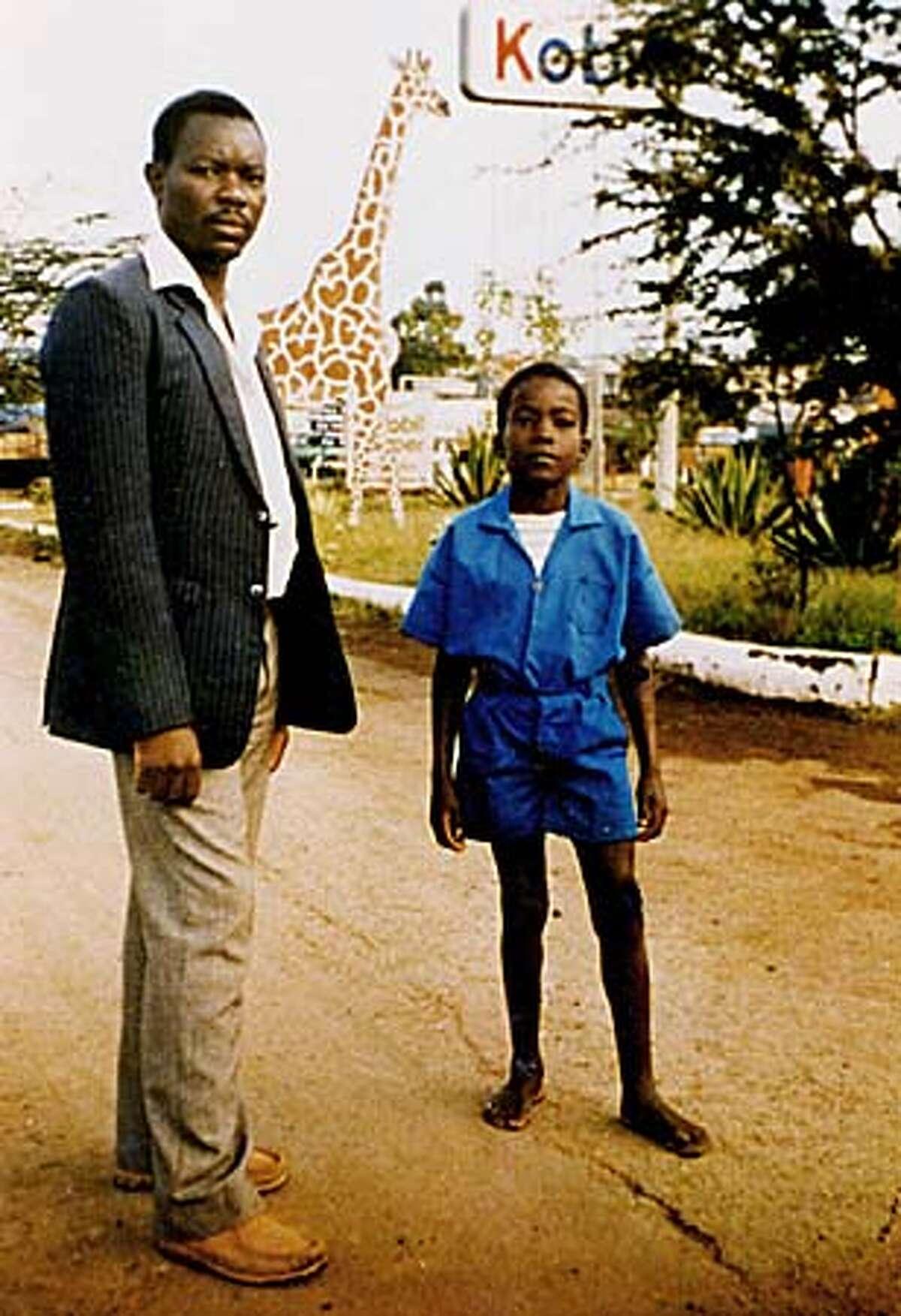 At age 10, Masai student Kimeli Naiyomah posed with his Kenyan primary school teacher S. Nyangeri.