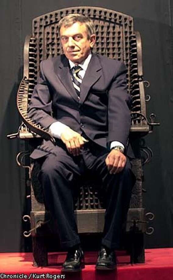 Aldo Migliorini, director of the Torture Exhibition at Herbst Hall, sat in an interrogation chair. Chronicle photo by Kurt Rogers