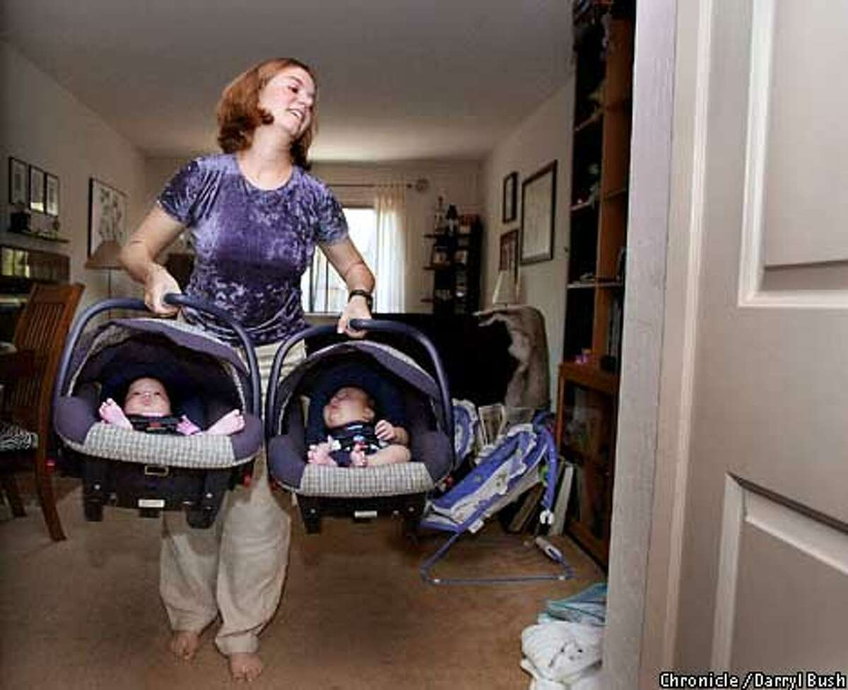 Mother Lynn Reda carries her twins; , Lochen (cq) a boy, as Solveig (cq) a girl, as they sit in their car seats as athey leave on their trip to the store in their home in Mountain View. Chronicle Photo by Darryl Bush