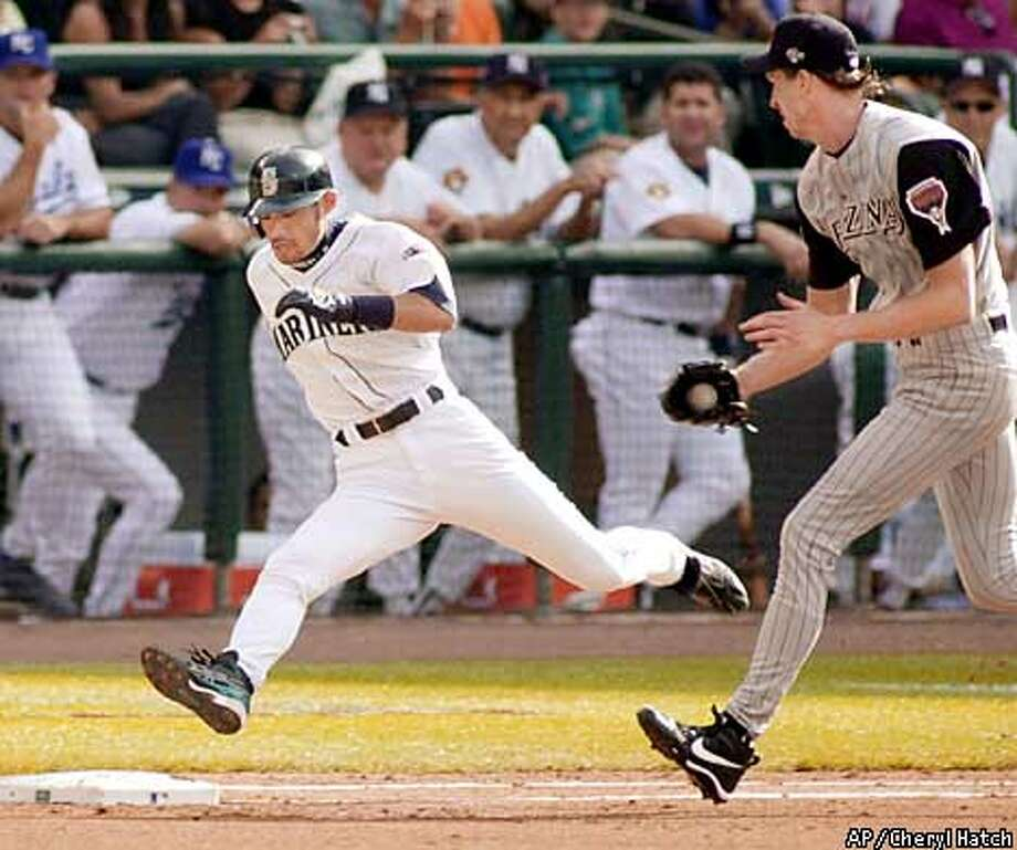 Seattle Mariners' Ichiro Suzuki legs out an infield hit as National Leagues starting pitcher Randy Johnson pursues him during the first inning of the in Seattle Tuesday, July 10, 2001. (AP Photo/Cheryl Hatch) Photo: CHERYL HATCH