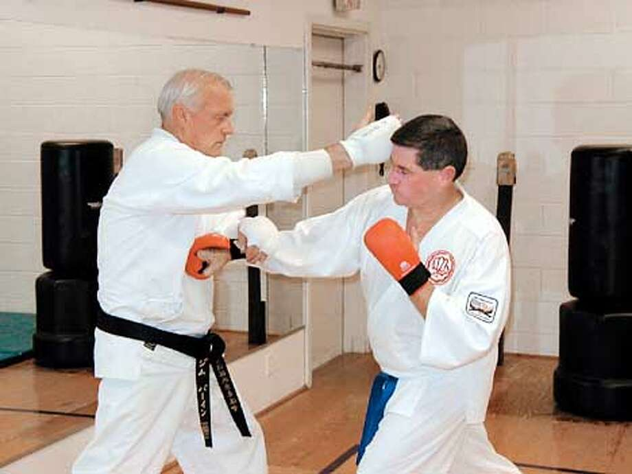 "Jim Byrd, 54 (right), of Dublin perfects his karate chops with James Byrne of San Ramon at the All American Black Belt Academy. Byrd made a deal with his daughter Christy, 8, that if she stuck with karate for three months, he'd join too. Three months later, Christy told him, ""I love karate. Now it's your turn, Dad."""