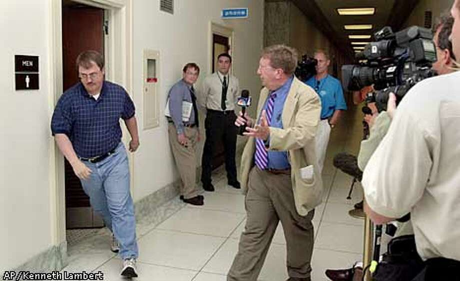 Randy Groves, left, legislative director for Rep. Gary Condit, D-Calif., storms out of a men's room down the hall from Condit's office, on Capitol Hill, as he is questioned by local NBC television reporter Pat Collins, center, Monday, July 9, 2001, in Washington. Groves, who had handled much of the media relations the past nine weeks for Condit, since intern Chandra Levy's disappearance, was at one point followed into the bathroom by Collins. Condit has reportedly admitted to having an affair with Levy. (AP Photo/Kenneth Lambert) Photo: KENNETH LAMBERT