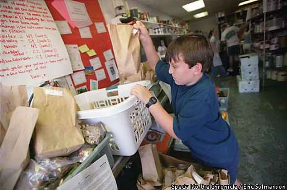 NBVOLUNTEERC/C/10OCT99/NF/SPCL --- Christopher J. Stein, 11, sorts through his day's shipments as a volunteer delivering warm meals for Meals of Marin, based in San Rafael. MUST CREDIT: ERIC SLOMANSON/SPECIAL TO THE CHRONICLE  ONE TIME USE ONLY; FOR PRICING AND RIGHTS TO USE YOU MUST CONTACT: 415-298-9948 Photo: ERIC SLOMANSON