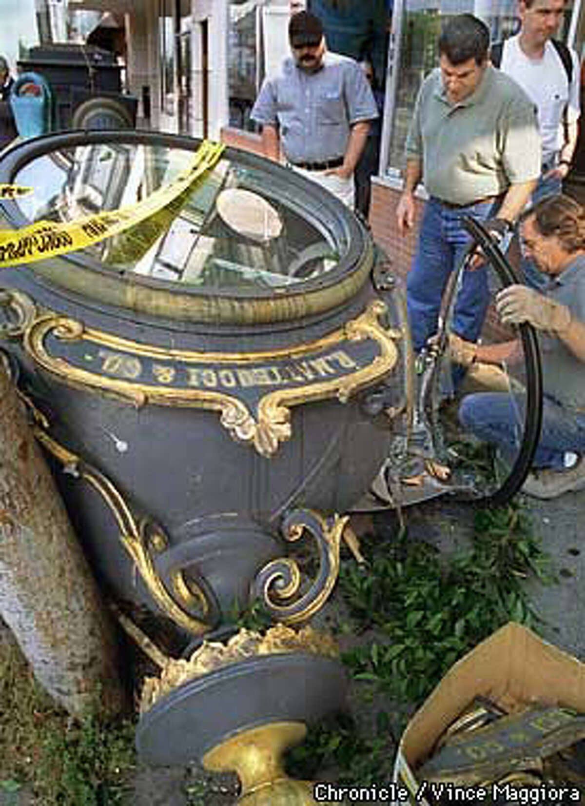 People who rushed to the scene of the toppled street clock on Columbus Avenue picked up some of the many broken parts. Chronicle Photo by Vince Maggoria