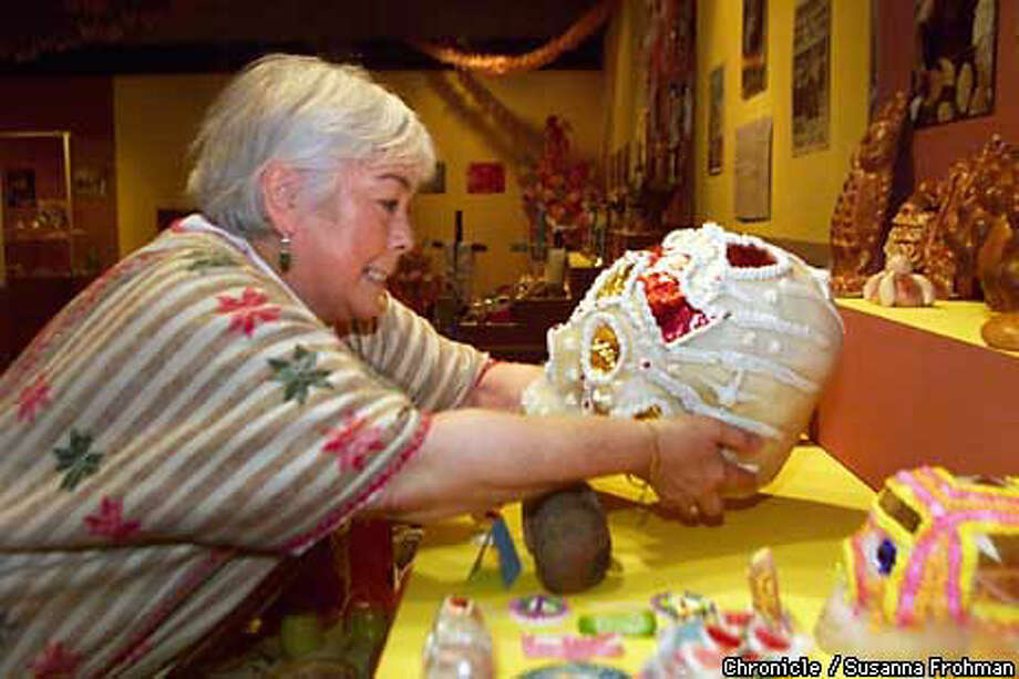"Yolanda Garfias Woo gently placed a delicate sugar skull nameds Pilar near other Day of the Dead offerings for the Oakland Museum exhibition ""El Color de la Muerte."" Chronicle Photo by Susanna Frohman"