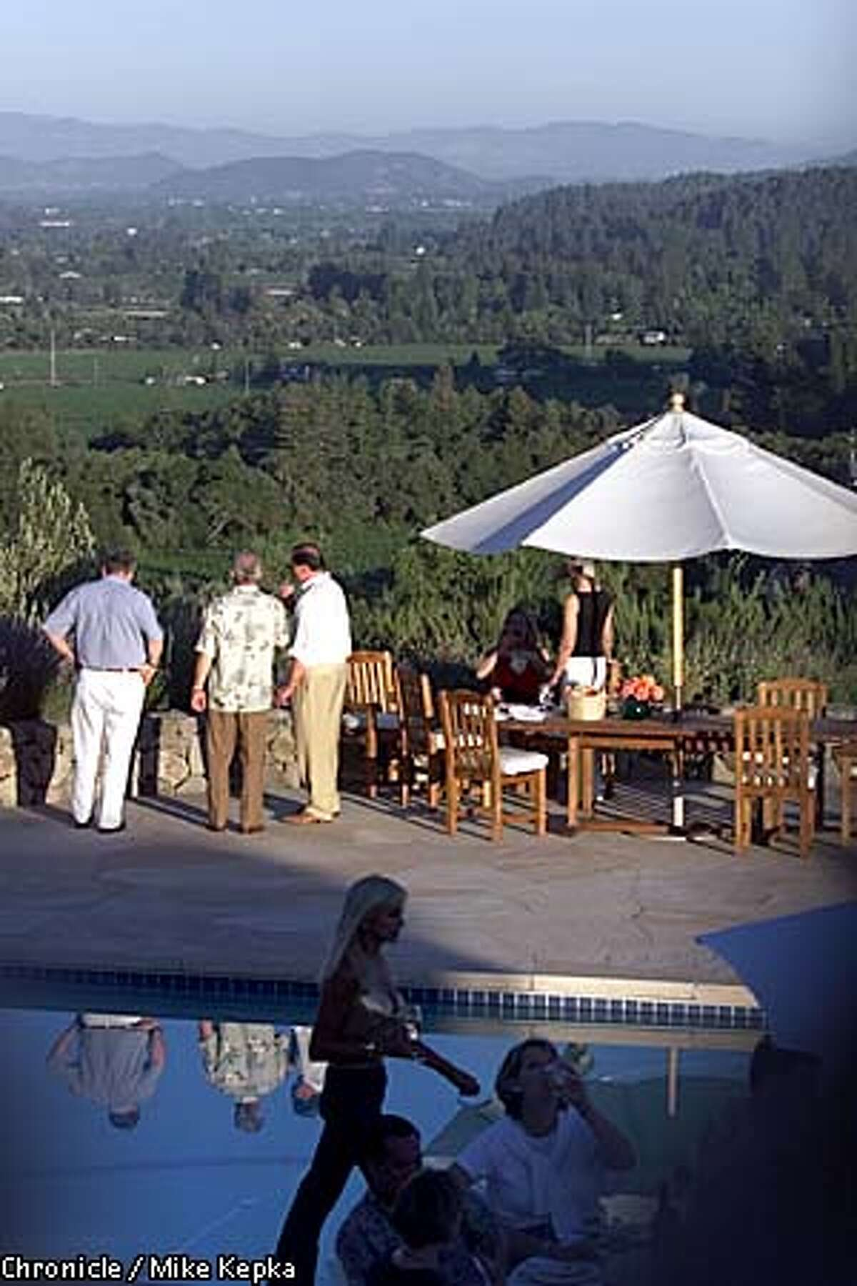 Party guests at Lord and Lady Butler's St. Helena estate drink in the views of Napa Valley from the back patio. Chronicle photo by Mike Kepka