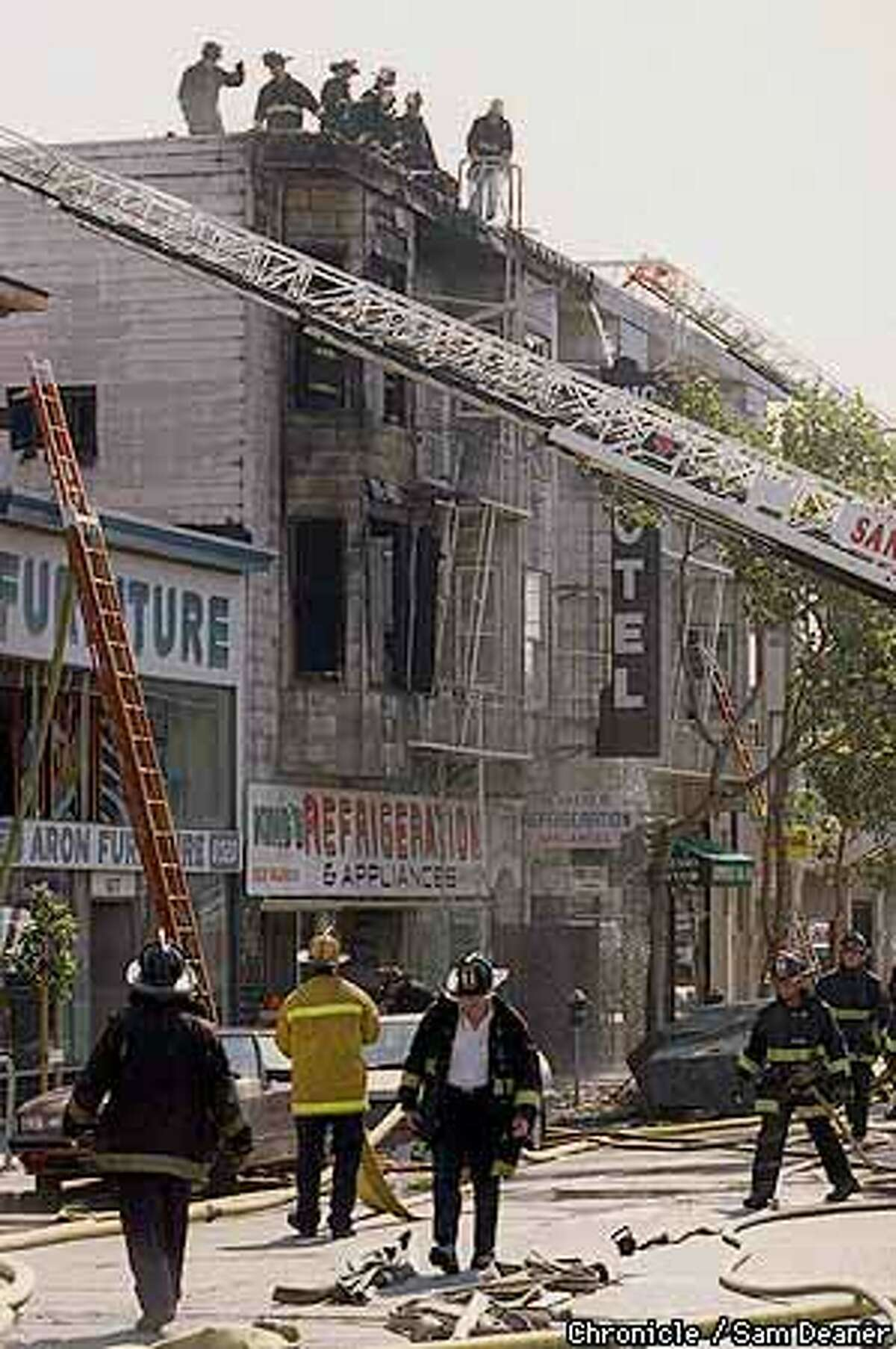 Firefighters doused the blaze that killed a tenant at ehe Mission District hotel. Chronicle Photo by Sam Deaner