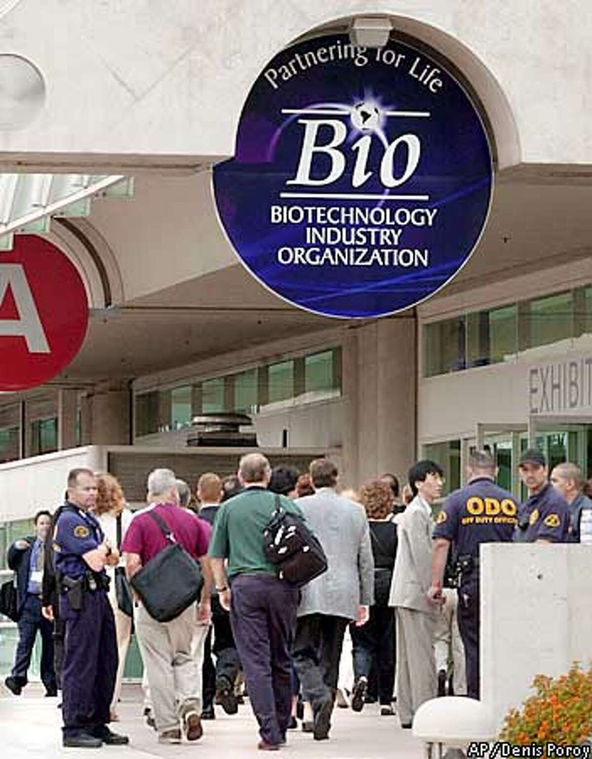 Biotech convention attendees enter the San Diego Convention Center under tight security for the first full day of the biotech convention Monday, June 25, 2001. The expected large protests were absent from the opening plenary breakfast. (AP Photo/Denis Poroy)