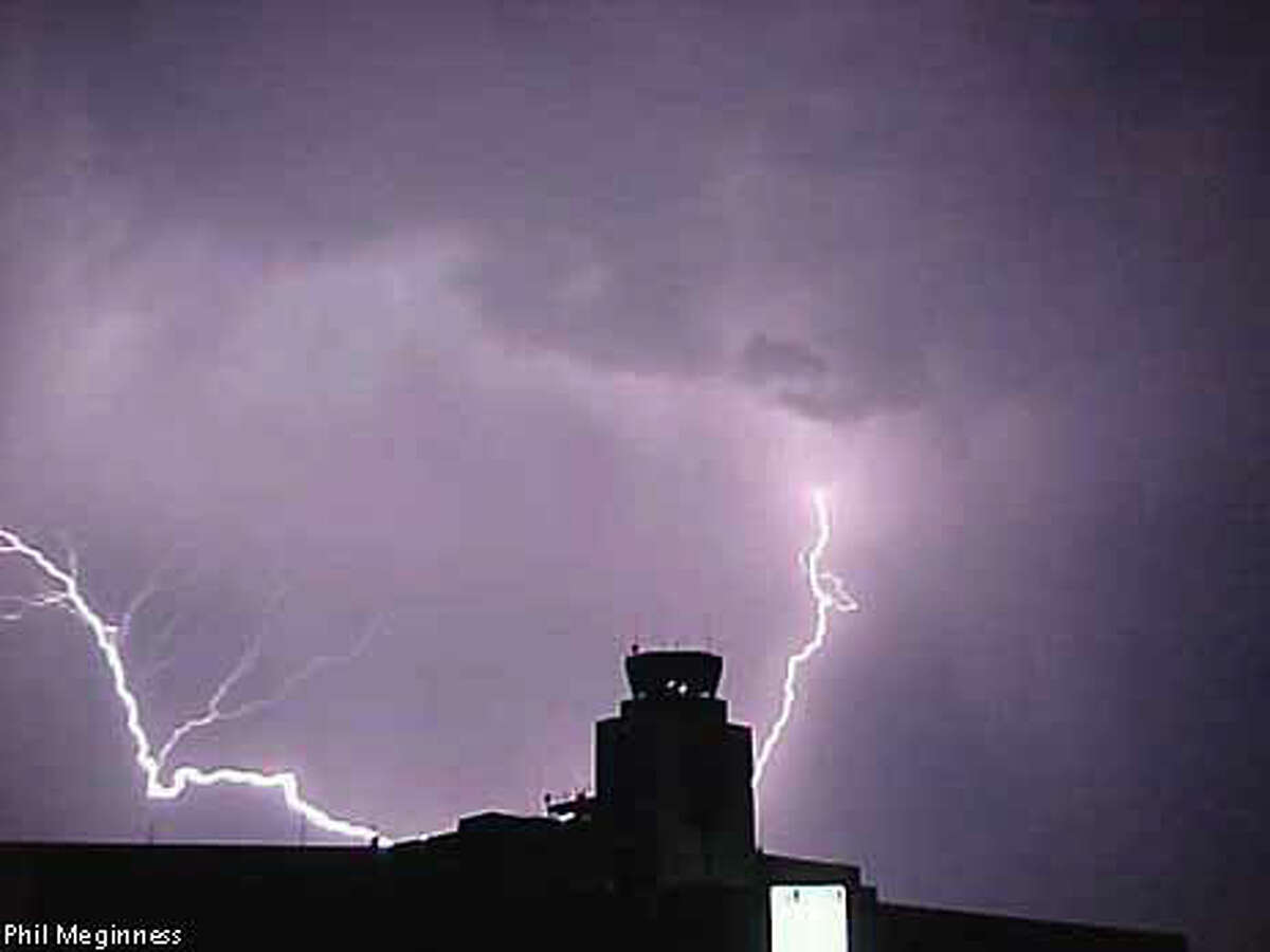 Lightning bolts flashed about 1 a.m. yesterday near the control tower at San Francisco International Airport: the unusual weather delayed flights all day. Photo by Paul Meginness