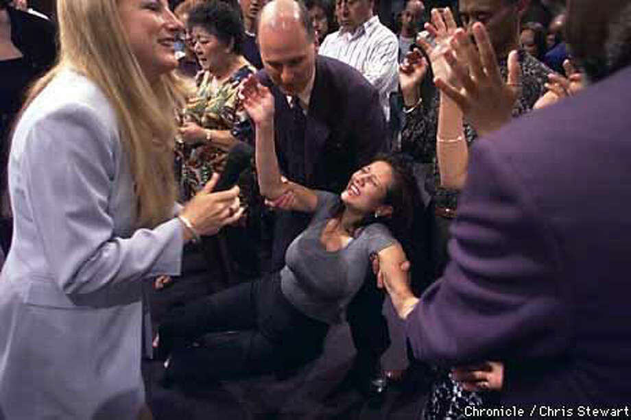 A woman was overcome during a laying on of hands by the Rev. Carla Bernal (left) during a service at Jubilee Christian Center in San Jose.  Chronicle Photo by Chris Stewart