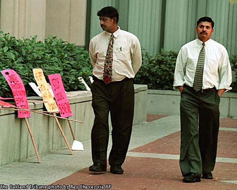 Vijay Lakireddy, left, and brother Prasad, passed a line of signs protesting their father, Lakireddy Bali Reddy, as they entered the federal court building in Oakland, Tuesday.  Oakland Tribune photo by Ray Chavez via Associated Press