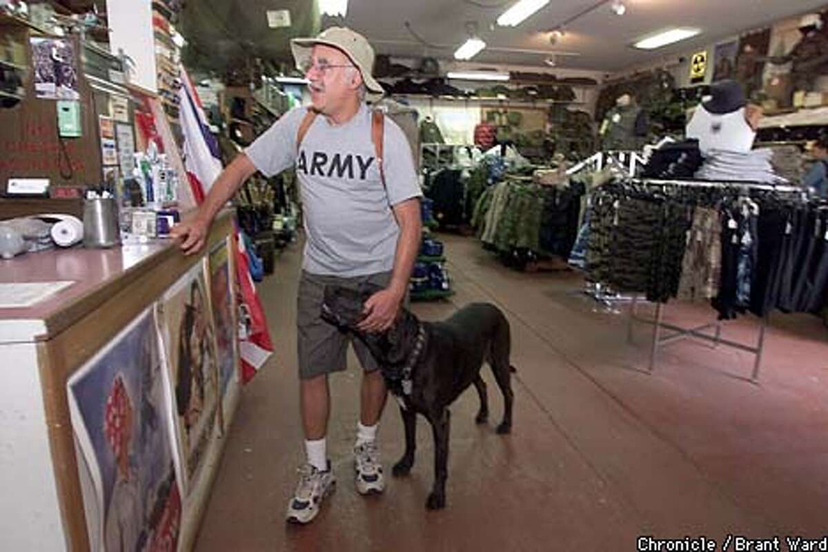 Surplus-store owner Jerry Kerson, who always dresses the part, and his dog, Panda, toured the aisles in search of bargains. Chronicle photo by Brant Ward