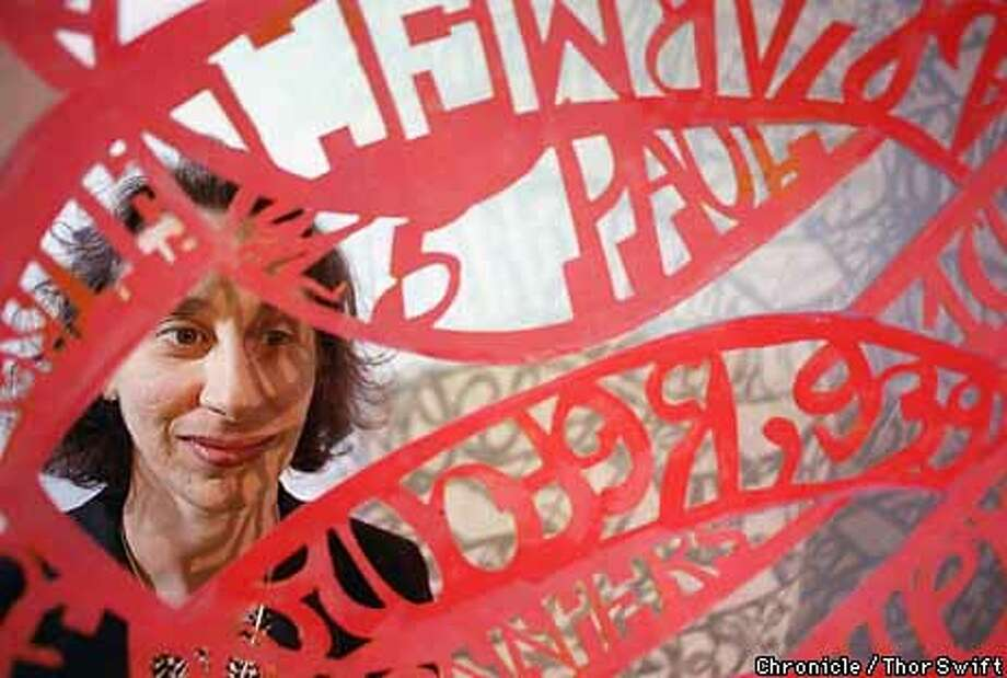 """Constance Wolf, guest curator at the San Francisco Art Institute, stands behind """"Cutting From a Gradual"""", mixed media on cut paper, which is part of a show about spirituality and otherworldiness.  BY THOR SWIFT/THE CHRONICLE Photo: THOR SWIFT"""