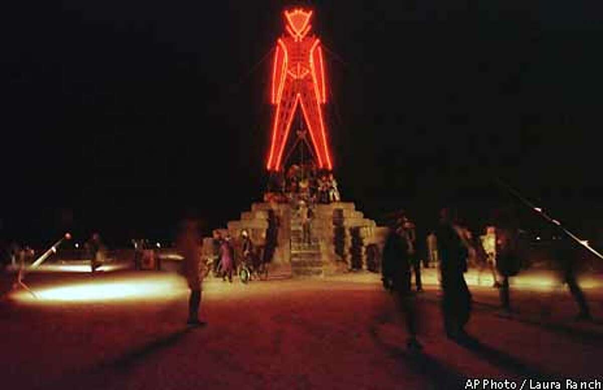 The symbolic man stands glowing in the desert as visitors wander around him during the festival in the Black Rock Desert near Gerlach, Nev., Thursday, Sept. 2, 1999. The gathering, intended to be a celebration of radical free expression and self reliance, will host 20,000 people before its culmination on Saturday where the statue of the man will be set on fire. (AP Photo/Laura Rauch)