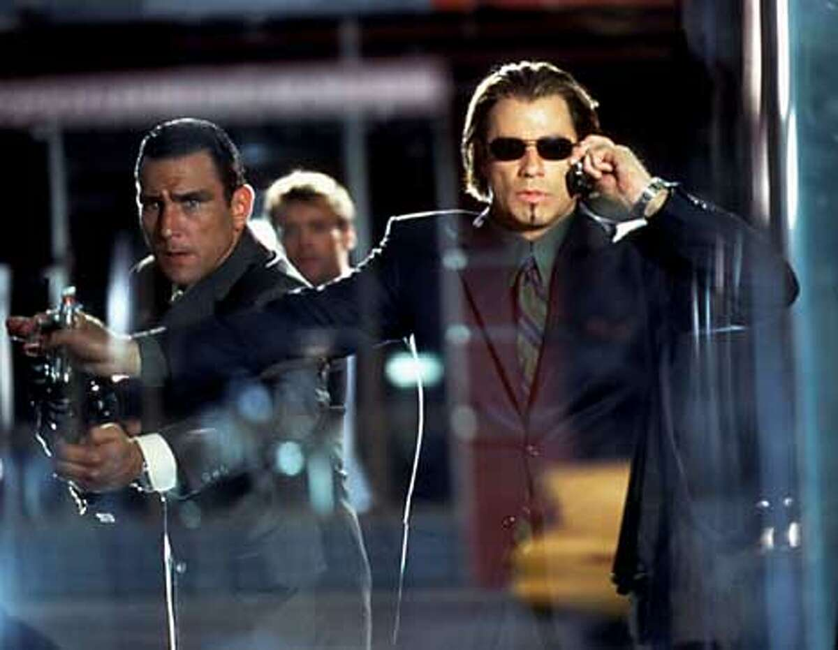 """Actors John Travolta (R) and Vinnie Jones are pictured in a scene from the new counter-espionage action thriller """"Swordfish,"""" opening nationwide June 8, 2001. The film also stars Halle Berry and Hugh Jackman. REUTERS/Andrew Cooper/Warner Bros. and Village Roadshow Films Handout"""