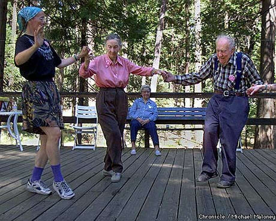 91 year old Louis Dubay (right) and his wife Leonora Bravo 85, center)  learn a few greek dance steps from instructor Edith Bourbin. Camp Mather is  a city run camp now celebrating it's 75th year. Over 170 seniors relived  their youth and camped out at the site near Yosemite.  Chronicle Photo by Michael Maloney