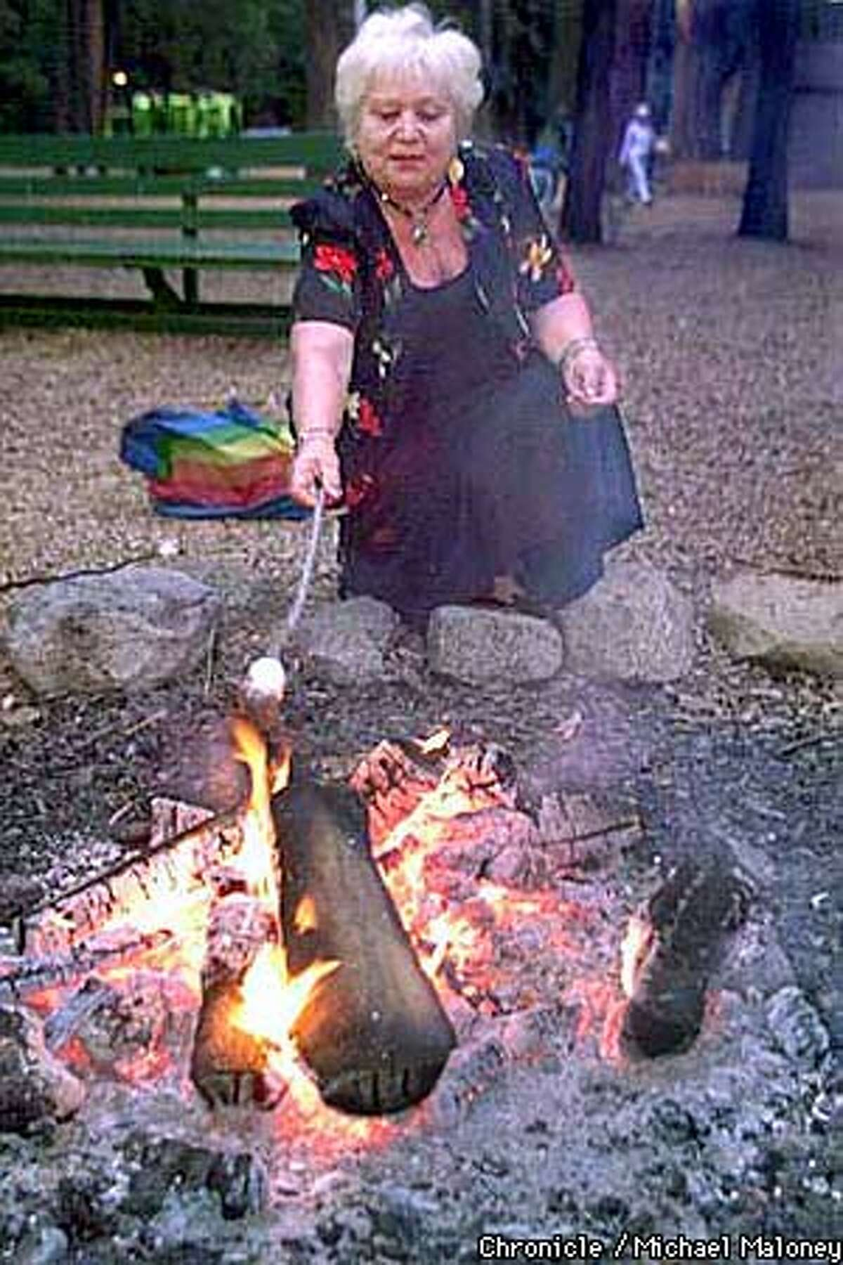 63 year old Adele Bantov roasts marshmallows for the first time over an open campfire. She was wearing a dress to participate in a social gathering at the Evergreen Lodge later in the evening. Camp Mather is a city-run camp now celebrating its 75th year. Over 170 seniors relived their youth and camped out at the site near Yosemite. Chronicle Photo by Michael Maloney