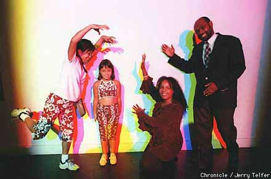 Irene Acosta (left), daughter Makaela Haeger, Darlene Librero, director of the Exploratorium's explainer program, and Reginald Smith cast shadows on a wall as colored lights shone on them from different angles. Jerry Telfer/The Chronicle